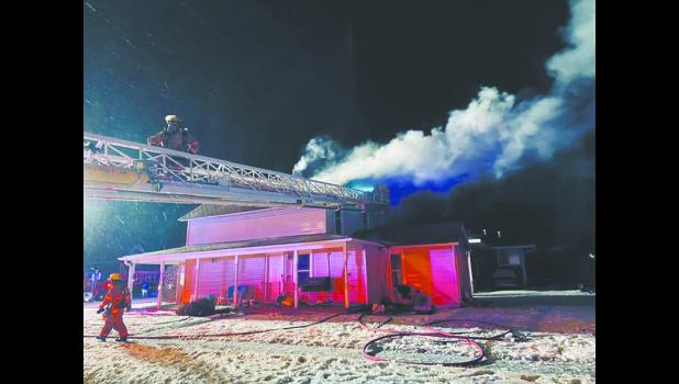 Ashland firefighters access the roof of a home on fire by using the aerial ladder due to icy conditions. While fighting the fire, a marijuana grow operation was discovered in the house and one person was arrested. Photo by Tiffany Alcorn, Ashland Rescue.