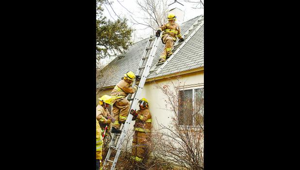 During roof ventilation training, Tim Rotert, Layton Schimke and Ryan Jungemann practice drills to ventilate a smoke-filled house.